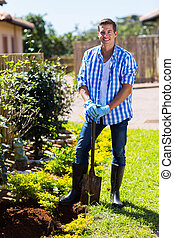 happy man with a spade in the garden - happy young man with...