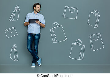 Happy man with a tablet smiling while doing shopping online