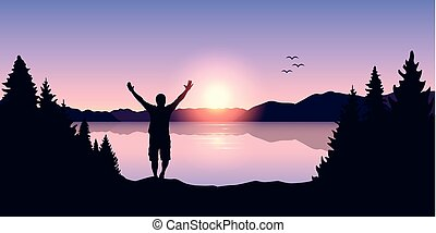 happy man with arms raised at sunrise at the lake