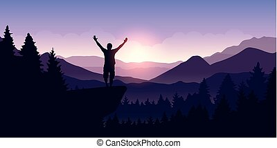 happy man with arms raised stands on top of a cliff in mountain landscape at sunrise
