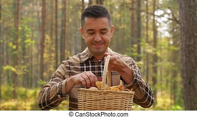 picking season and leisure people concept - happy smiling middle aged man with wicker basket of mushrooms in autumn forest