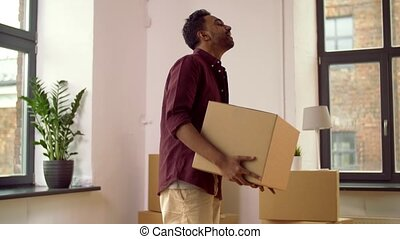 happy man with box moving to new home and dancing