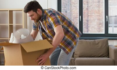happy man with box moving to new home - moving, people and...