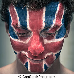 Happy man with British flag on face looking down