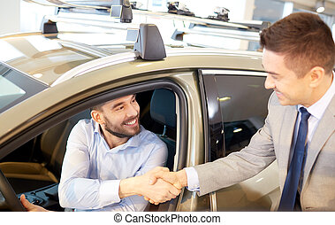 happy man with car dealer in auto show or salon