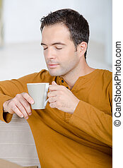 happy man with cup of tea at home