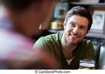 happy man with friend drinking beer at bar or pub - people,...