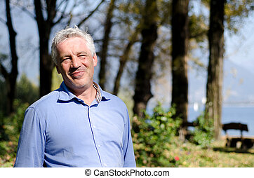 Happy man with grey hair standing up in the nature and smiling