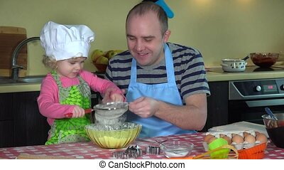 Happy man with his adorable daughter girl sifting flour for cake baking