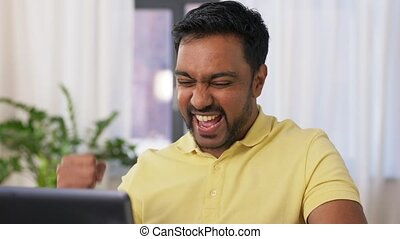 happy man with laptop working at home office