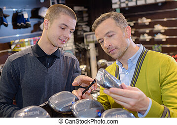 happy man with man selecting golf club in store
