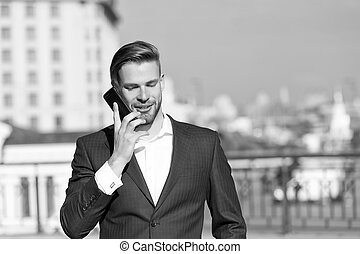 Happy man with mobile phone on sunny terrace. Businessman use smartphone with smile. Great business news. Business communication. Communication and agile business. New technology and modern life