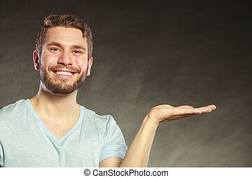 Happy man with open empty hand palm for copy space