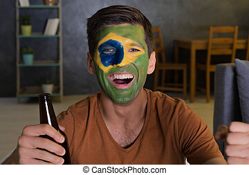 Happy man with painted flag of Brazil