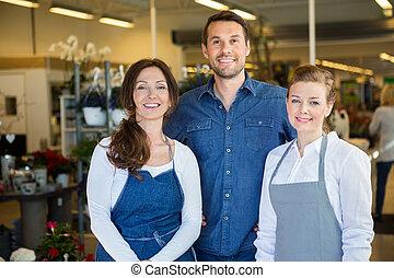 Happy Man With Salesgirls In Flower Shop