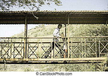Happy man with small girl walking on bridge