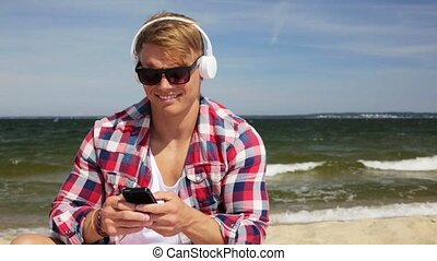 happy man with smartphone and headphones on beach - summer...