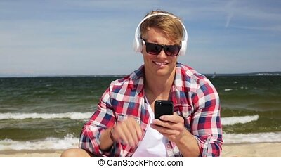 happy man with smartphone and headphones on beach