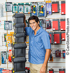Happy Man With Stacked Toolboxes In Store