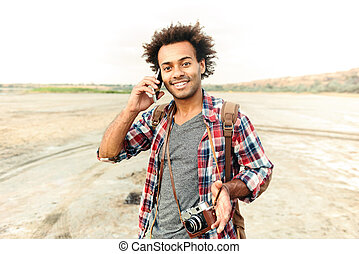 Happy man with vintage photo camera talking on mobile phone