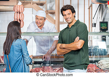 Happy Man With Woman Buying Meat At Butchery