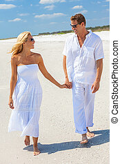 Happy Man Woman Couple Holding Hands Walking on a Beach