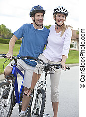 Happy Man & Woman Couple Riding Bikes