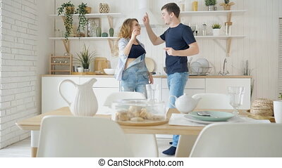 happy man woman dance by served table in modern kitchen -...