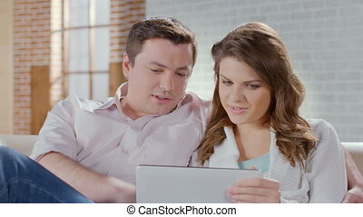 Happy man woman enjoying time together, online shopping, tablet