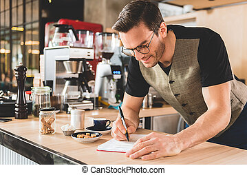 Happy man writing recipe of appetizing beverage - Cheerful...