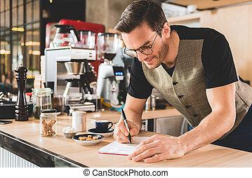 Happy man writing recipe of appetizing beverage - Cheerful...