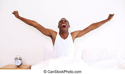 Happy man yawning and stretching sitting in bed at home in...