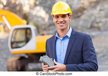 manager in mining site holding ore - happy manager in mining...
