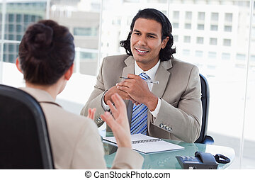 Happy manager interviewing a female applicant in his office