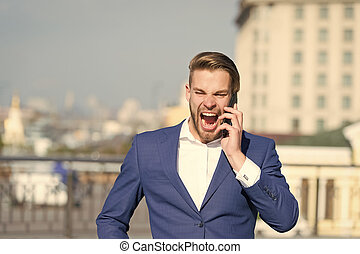 Happy manager talk on smartphone. Man with mobile phone on sunny terrace. Businessman in blue suit outdoor. Business communication, new technology and sms. Modern life and business lifestyle