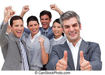 Happy manager with thumbs up standing with his team against...