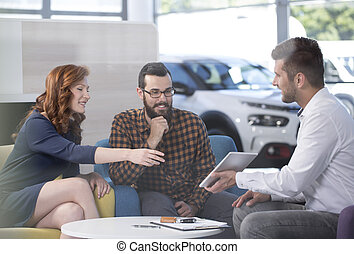 Happy marriage choosing new car while talking with seller in the showroom