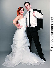 Happy married couple bride groom on gray background
