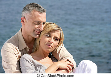 Happy married couple by the sea
