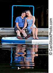 Happy married couple in marina with paddle board floating on water.