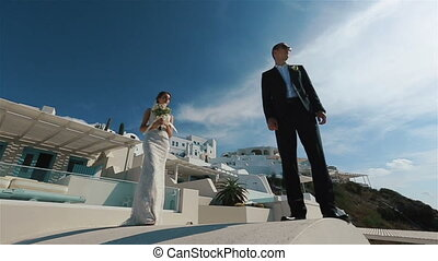 Happy married couple meeting and kissing on terrace with sea background, Santorini closeup