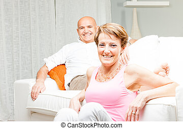 Happy married couple relaxing at home together