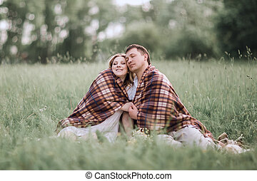 happy, married couple sitting together under a warm blanket on the lawn