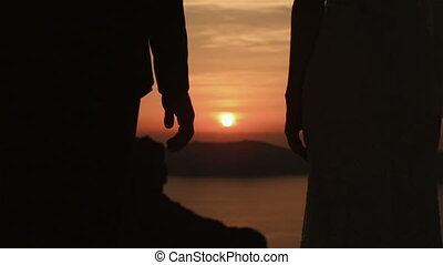 Happy married couple softly holding hands close up at sunset sky background
