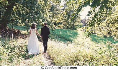 Happy married couple walk together in the park. Slowly