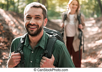 Happy married couple walking in the woods with enjoyment