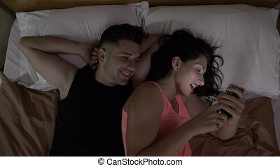 Happy married couple watching a funny video on social media on a smartphone on the bed at home