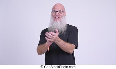 Happy mature bald bearded man clapping hands - Studio shot...