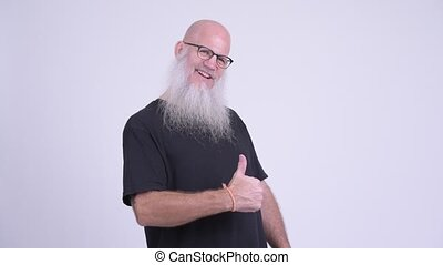 Happy mature bald bearded man giving thumbs up - Studio shot...