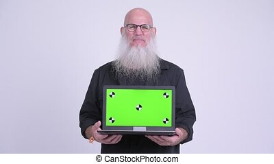 Happy mature bald bearded man showing laptop
